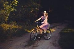 Όμορφο κορίτσι που φορά ένα συμπαθητικό ρόδινο φόρεμα που έχει τη διασκέδαση σε ένα πάρκο με ένα ποδήλατο που κρατά ένα όμορφο κα Στοκ Φωτογραφία