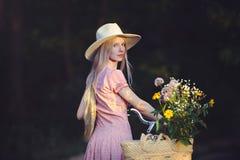 Όμορφο κορίτσι που φορά ένα συμπαθητικό ρόδινο φόρεμα που έχει τη διασκέδαση σε ένα πάρκο με ένα ποδήλατο που κρατά ένα όμορφο κα Στοκ Φωτογραφίες