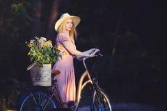 Όμορφο κορίτσι που φορά ένα συμπαθητικό ρόδινο φόρεμα που έχει τη διασκέδαση σε ένα πάρκο με ένα ποδήλατο που κρατά ένα όμορφο κα Στοκ Εικόνες