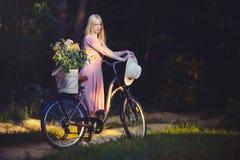 Όμορφο κορίτσι που φορά ένα συμπαθητικό ρόδινο φόρεμα που έχει τη διασκέδαση σε ένα πάρκο με ένα ποδήλατο που κρατά ένα όμορφο κα Στοκ εικόνα με δικαίωμα ελεύθερης χρήσης