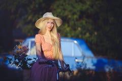 Όμορφο κορίτσι που φορά ένα συμπαθητικό φόρεμα που έχει τη διασκέδαση σε ένα εξοχικό σπίτι με ένα ποδήλατο, που κρατά ένα όμορφο  Στοκ φωτογραφία με δικαίωμα ελεύθερης χρήσης
