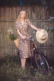 Όμορφο κορίτσι που φορά ένα συμπαθητικό φόρεμα που έχει τη διασκέδαση σε ένα πάρκο με ένα ποδήλατο που κρατά ένα όμορφο καλάθι με Στοκ εικόνα με δικαίωμα ελεύθερης χρήσης