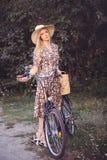 Όμορφο κορίτσι που φορά ένα συμπαθητικό φόρεμα που έχει τη διασκέδαση σε ένα πάρκο με ένα ποδήλατο που κρατά ένα όμορφο καλάθι με Στοκ Εικόνες