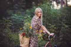 Όμορφο κορίτσι που φορά ένα συμπαθητικό φόρεμα που έχει τη διασκέδαση σε ένα πάρκο με ένα ποδήλατο που κρατά ένα όμορφο καλάθι με Στοκ φωτογραφίες με δικαίωμα ελεύθερης χρήσης