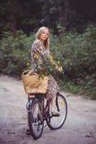 Όμορφο κορίτσι που φορά ένα συμπαθητικό φόρεμα που έχει τη διασκέδαση σε ένα πάρκο με ένα ποδήλατο που κρατά ένα όμορφο καλάθι με Στοκ εικόνες με δικαίωμα ελεύθερης χρήσης