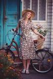 Όμορφο κορίτσι που φορά ένα συμπαθητικό φόρεμα που έχει τη διασκέδαση σε ένα εξοχικό σπίτι με ένα ποδήλατο, που κρατά ένα όμορφο  Στοκ Εικόνες
