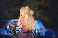 Όμορφο κορίτσι που φορά ένα συμπαθητικό φόρεμα που έχει τη διασκέδαση σε ένα εξοχικό σπίτι με ένα ποδήλατο, που κρατά ένα όμορφο  Στοκ εικόνες με δικαίωμα ελεύθερης χρήσης