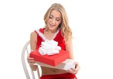 Όμορφο κορίτσι που φορά τα κόκκινα ενδύματα Άγιου Βασίλη με το δώρο χριστουγεννιάτικου δώρου στοκ φωτογραφία