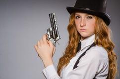 Όμορφο κορίτσι που φορά το αναδρομικό καπέλο και που κρατά το όπλο Στοκ Εικόνες