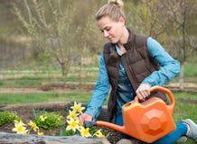 Όμορφο κορίτσι που φροντίζει τον κήπο Πότισμα των λουλουδιών από το waterin στοκ φωτογραφία