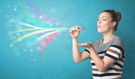 Όμορφο κορίτσι που φυσά τις αφηρημένες ζωηρόχρωμες φυσαλίδες και τις γραμμές Στοκ Φωτογραφίες
