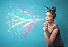 Όμορφο κορίτσι που φυσά τις αφηρημένες ζωηρόχρωμες φυσαλίδες και τις γραμμές Στοκ Φωτογραφία