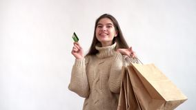 Όμορφο κορίτσι που χαμογελά και που κρατά τις συσκευασίες με τις αγορές και την κάρτα πληρωμής φιλμ μικρού μήκους