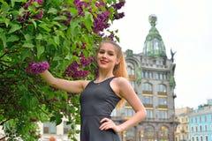 Όμορφο κορίτσι που χαμογελά το Μπους των πορφυρών πασχαλιών στο υπόβαθρο ο Στοκ Εικόνες