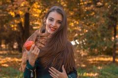 Όμορφο κορίτσι που χαμογελά και που κρατά την κόκκινη Apple διαθέσιμη Στοκ Εικόνες