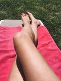Όμορφο κορίτσι που χαλαρώνει τα πόδια της στη ρόδινη πετσέτα Στοκ Φωτογραφία