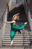 Όμορφο κορίτσι που χορεύει στην πόλη ενάντια στο σκηνικό μιας σκάλας πετρών Στοκ Φωτογραφία