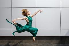 Όμορφο κορίτσι που χορεύει στην πόλη και που πηδά στο κλίμα τοίχων Στοκ Εικόνες