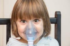Όμορφο κορίτσι που χρησιμοποιεί τη μάσκα εισπνοής στοκ φωτογραφίες