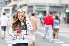 Όμορφο κορίτσι που χρησιμοποιεί το έξυπνο τηλέφωνο στην οδό, σύγχρονος τρόπος ζωής Στοκ εικόνες με δικαίωμα ελεύθερης χρήσης