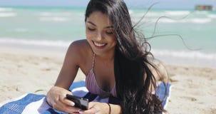 Όμορφο κορίτσι που χρησιμοποιεί το τηλέφωνο στην παραλία απόθεμα βίντεο