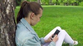 Όμορφο κορίτσι που χρησιμοποιεί Smartphone στο πάρκο φιλμ μικρού μήκους