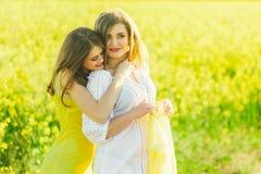 όμορφο κορίτσι 2 σε έναν τομέα των κίτρινων λουλουδιών Mom με κόρη ή δύο αδελφές που αγκαλιάζει στα πλαίσια ενός τομέα Στοκ φωτογραφίες με δικαίωμα ελεύθερης χρήσης