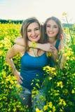 όμορφο κορίτσι 2 σε έναν τομέα των κίτρινων λουλουδιών Mom με κόρη ή δύο αδελφές που αγκαλιάζει στα πλαίσια ενός τομέα Στοκ φωτογραφία με δικαίωμα ελεύθερης χρήσης