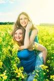 όμορφο κορίτσι 2 σε έναν τομέα των κίτρινων λουλουδιών Mom με κόρη ή δύο αδελφές που αγκαλιάζει στα πλαίσια ενός τομέα Στοκ Φωτογραφία