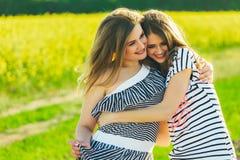 όμορφο κορίτσι 2 σε έναν τομέα των κίτρινων λουλουδιών Mom με κόρη ή δύο αδελφές που αγκαλιάζει στα πλαίσια ενός τομέα Στοκ Εικόνα
