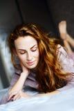 Όμορφο κορίτσι σε ένα κρεβάτι Στοκ Εικόνες