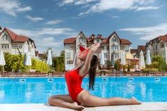 Όμορφο κορίτσι σε ένα κόκκινο κοστούμι λουσίματος σε ένα όμορφο ξενοδοχείο κοντά στη λίμνη στοκ εικόνα