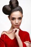 Όμορφο κορίτσι σε ένα κόκκινο πουκάμισο και λαμπρές καρδιές στο μάγουλό της Πρότυπο με ένα τόξο στο επικεφαλής και Nude makeup τη Στοκ Εικόνες