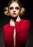 Όμορφο κορίτσι σε ένα κόκκινο φόρεμα με ένα βαθύ neckline και μαύρα δαχτυλίδια στα δάχτυλά του Το πρότυπο με το φωτεινό makeup Στοκ Φωτογραφίες