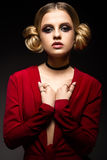 Όμορφο κορίτσι σε ένα κόκκινο φόρεμα με ένα βαθύ neckline και μαύρα δαχτυλίδια στα δάχτυλά του Το πρότυπο με το φωτεινό makeup Στοκ φωτογραφίες με δικαίωμα ελεύθερης χρήσης