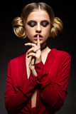 Όμορφο κορίτσι σε ένα κόκκινο φόρεμα με ένα βαθύ neckline και μαύρα δαχτυλίδια στα δάχτυλά του Το πρότυπο με το φωτεινό makeup στοκ εικόνες