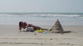 Όμορφο κορίτσι σε ένα μαγιό που κτυπά ένα άσπρο σκυλί στην παραλία 4K φιλμ μικρού μήκους
