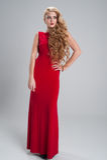 Όμορφο κορίτσι σε ένα μακρύ κόκκινο φόρεμα με τη μακροχρόνια σγουρή εκμετάλλευση τρίχας Στοκ Φωτογραφία