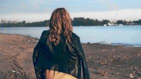 Όμορφο κορίτσι σε ένα μαύρο σακάκι που περπατά κοντά στον ποταμό και τον καφέ κατανάλωσης απόθεμα βίντεο
