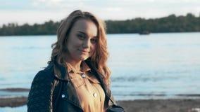 Όμορφο κορίτσι σε ένα μαύρο σακάκι που στέκεται κοντά στον ποταμό και τον καφέ κατανάλωσης απόθεμα βίντεο