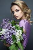 Όμορφο κορίτσι σε ένα πορφυρό φόρεμα και μια ανθοδέσμη των πασχαλιών Το πρότυπο είναι σε μια εικόνα της άνοιξη Στοκ Εικόνα