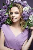 Όμορφο κορίτσι σε ένα πορφυρό φόρεμα και μια ανθοδέσμη των πασχαλιών Το πρότυπο είναι σε μια εικόνα της άνοιξη Στοκ εικόνα με δικαίωμα ελεύθερης χρήσης