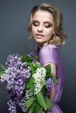 Όμορφο κορίτσι σε ένα πορφυρό φόρεμα και μια ανθοδέσμη των πασχαλιών Το πρότυπο είναι σε μια εικόνα της άνοιξη στοκ εικόνες