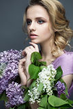 Όμορφο κορίτσι σε ένα πορφυρό φόρεμα και μια ανθοδέσμη των πασχαλιών Το πρότυπο είναι σε μια εικόνα της άνοιξη Στοκ Φωτογραφία