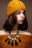 Όμορφο κορίτσι σε ένα πλεκτό καπέλο στο κεφάλι της και ένα περιδέραιο των μαργαριταριών γύρω από το λαιμό της Το πρότυπο με την ε Στοκ φωτογραφία με δικαίωμα ελεύθερης χρήσης