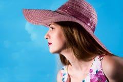 Όμορφο κορίτσι σε ένα ρόδινο καπέλο από τον ήλιο σε ένα σχεδιάγραμμα σε ένα μπλε Στοκ εικόνα με δικαίωμα ελεύθερης χρήσης