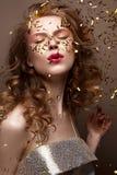 Όμορφο κορίτσι σε ένα φόρεμα βραδιού και χρυσές μπούκλες Το πρότυπο στη νέα εικόνα έτους ` s με ακτινοβολεί και tinsel Στοκ Εικόνες