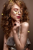 Όμορφο κορίτσι σε ένα φόρεμα βραδιού και χρυσές μπούκλες Το πρότυπο στη νέα εικόνα έτους ` s με ακτινοβολεί και tinsel στοκ φωτογραφία με δικαίωμα ελεύθερης χρήσης