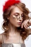 Όμορφο κορίτσι σε ένα χρυσό φόρεμα με μια ευγενή σύνθεση Πρότυπο με τα κόκκινα φτερά στο κεφάλι και τις μπούκλες της Φωτογραφία δ στοκ εικόνες