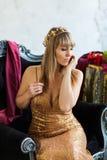 Όμορφο κορίτσι σε ένα χρυσό φόρεμα με μια κορώνα Στοκ Φωτογραφία